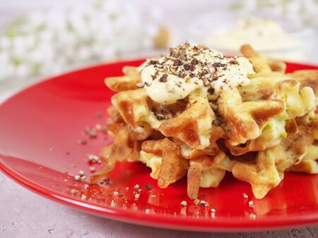 Zucchini waffles on a red plate with sauce and spices. Food concept.