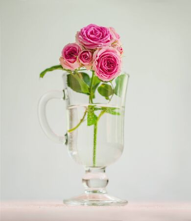 Romantic background: a branch of roses in a glass. A festive concept for Valentines Day, wedding, birthday, a significant date.