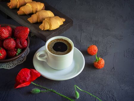 Vintage background with red poppies i, a cup of coffee, strawberries in a plate and croissants on a wooden tray