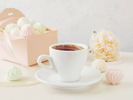 Pastel romantic background with coffee and small meringues in a box, flower and ribbons.