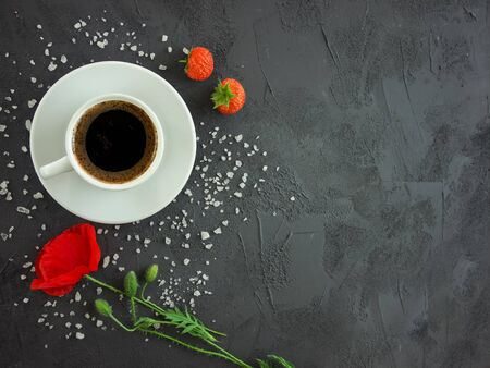 Cup with coffee on a texture table with poppy flower, strawberries and sprinkled chicken sugar