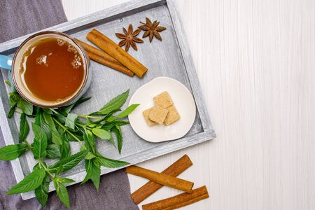 Breakfast. A cup of tea on a tray with a bunch of mint, starlets of anise and chopsticks of cinnamon