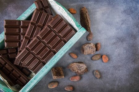 Chocolate bars in a vintage box. Chocolate beans, pieces of chocolate scattered on a textural background