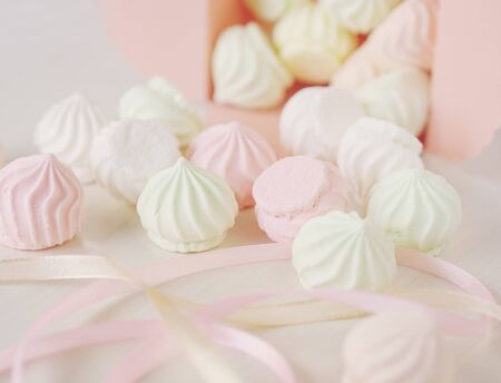 Pastel romantic background with scattered little meringues in a box, flower and ribbons