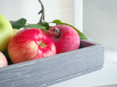 Autumn harvest: ripe, fragrant red-green apples in a wooden, gray box on a white chair. Food concept.