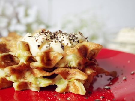 Zucchini waffles on a red plate with sauce and spices. Food concept.  Zdjęcie Seryjne