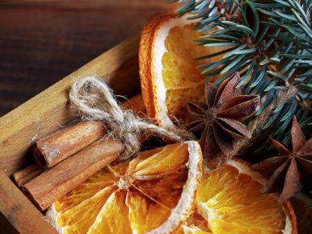 Christmas holiday composition : Beautiful close-up branches of spruce , of dry Oranges, Cinnamon sticks and star Anise  in  a wooden box.