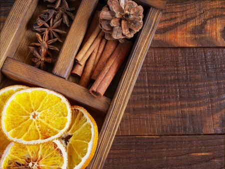 Christmas holiday composition : Beautiful close-up  of dry Oranges, Cinnamon sticks and star Anis, fir cones in  a wooden box on the wooden background. Top view. Flat lay Zdjęcie Seryjne