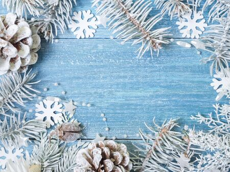 Christmas, New Year background. White spruce branches, cones, snowflakes on a blue wooden background. Top view. Close. Place for text. Zdjęcie Seryjne