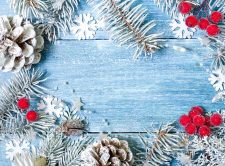Christmas, New Year background. White spruce branches, cones, snowflakes, red berries on a blue wooden background. Top view. Close. Place for text.