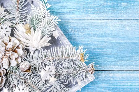 Christmas, New Year background. White spruce branches, cones, snowflakes  in  a wooden box , on a blue wooden background. Top view. Close. Place for text.