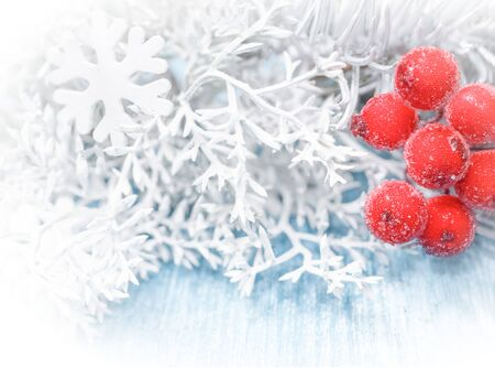 Christmas, New Year background. White spruce branches, cones, snowflakes, red berries on a blue wooden background. Close up.
