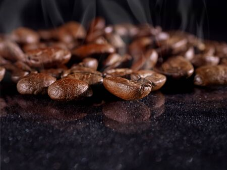 Hot coffee grains close on a black shiny background. Macro. Food concept