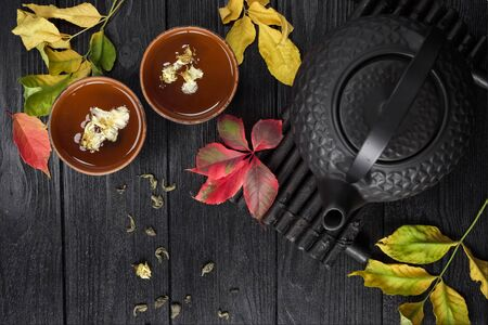 Black teapot and green tea with jasmine in a clay cup, on a black and wooden background with autumn leaves. Food concept. Top view