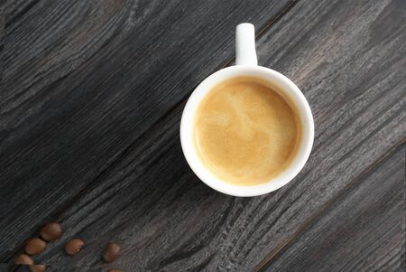 Morning espresso in a white cup on a gray, wooden background. Coffee beans are scattered around.