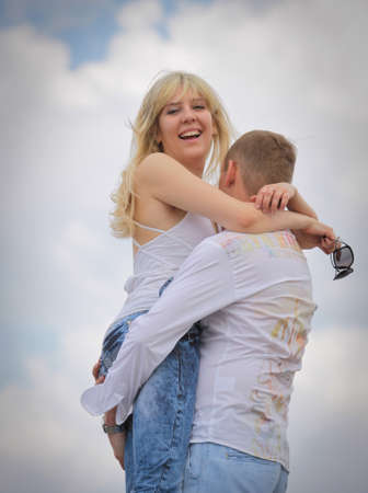 Young man holding his happy girlfriend against white clouds  photo