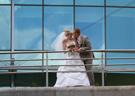 Bride and groom holding on their wedding walking photo