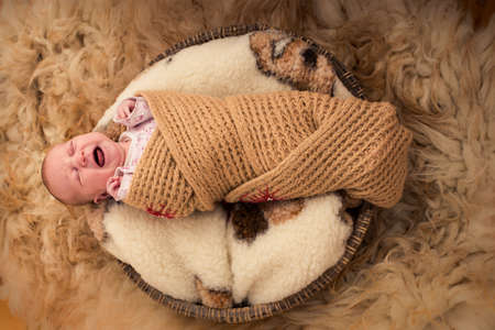 One month old baby crying in fury cover Stock Photo