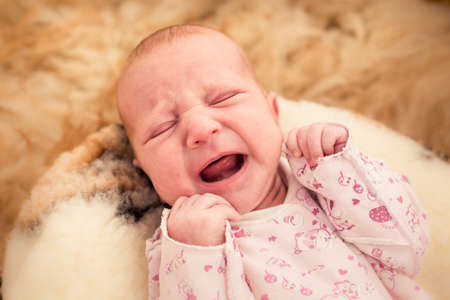 babyface: One month old baby crying in fury cover close up