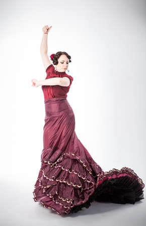 beautiful young brunette female spanish flamenco dancer in red blouse and vinous flamenco skirt dancing with her arms and flying skirt in studio on gray background photo