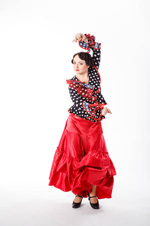 spanish ethnicity: young beautiful brunette female spanish flamenco dancer in black shirt and red flamenco skirt dancing with her arms in studio on gray background