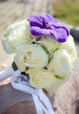 Bridal bouquet made from white roses with lilac orchid photo