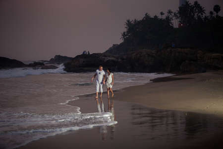 beautiful young couple in white walking and holding hands on the seashore near waves in the evening photo