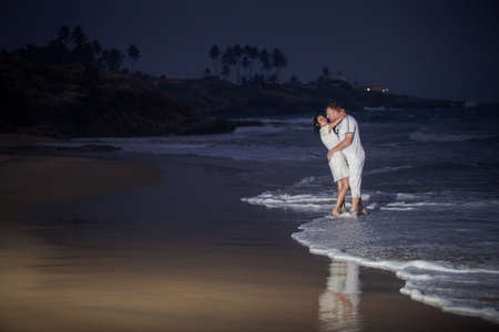 beautiful young couple in white kissing on the seashore near waves in the evening photo