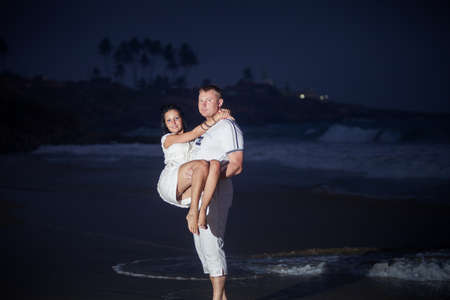 big man carry  his beautiful young girl in white dress on the seashore near waves in the evening photo