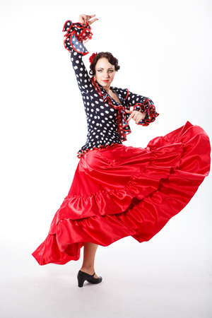 young beautiful brunette female spanish flamenco dancer in black shirt and red flamenco skirt dancing with her arms in studio on gray background photo
