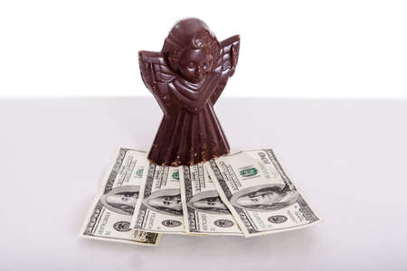 legal tender: milk chocolate angel figure with dollars on gray table