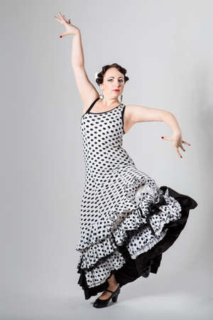 spanish ethnicity: beautiful brunette female young beautiful brunette female spanish flamenco dancer in black and white flamenco dress dancing in studio on gray background