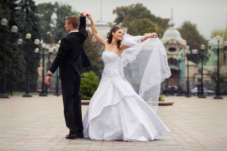 young handsome groom in black suit dance with his beautiful brunette bride in white wedding dress on big city background