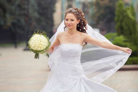 beautiful brunette bride in white wedding dress hold her bridal bouquet made from white roses and dance on city park background Stock Photo