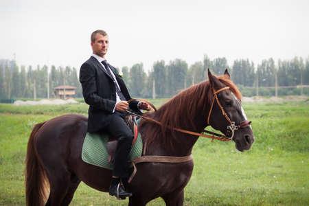 黒のスーツでハンサムな若い新郎馬に乗る 写真素材 - 31723126