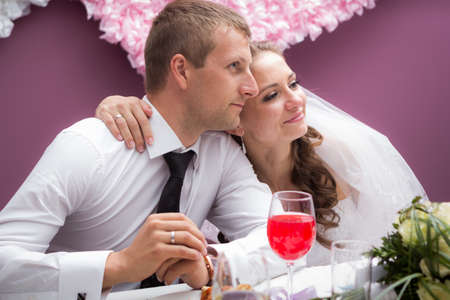 young groom and bride  in restaurant sit by banquet table photo