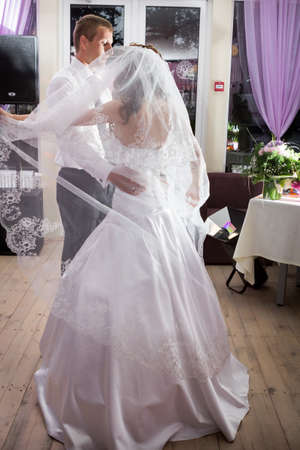beautiful groom and bride dance on banquet in restaurant photo