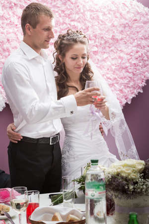 Handsome groom hold his young beautiful bride in restaurant by banquet table photo