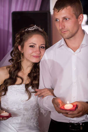 Handsome groom and young beautiful bride hold candles in restaurant photo