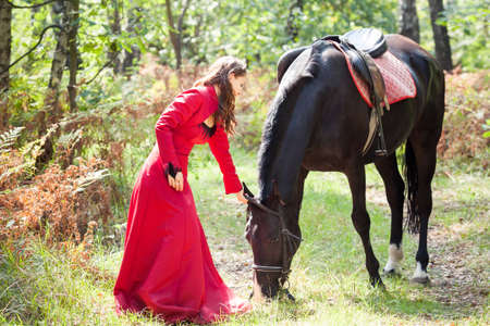 young beautiful brunette girl  in red dress  hold black horse in green forest photo