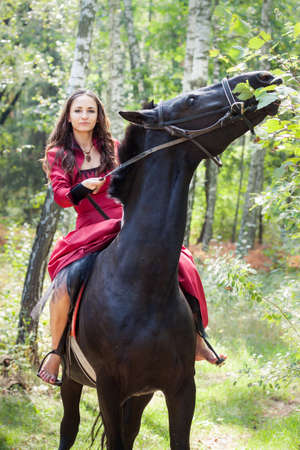 young beautiful brunette girl sit on a back of black horse in  green forest photo