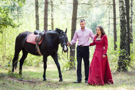 handsome man in pink shirt hold young beautiful brunette girl in long red dress walk with black horse in green forest photo