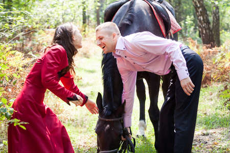 young beautiful brunette girl  in red dress walk with handsome man in pink shirt hold black horse in green forest photo