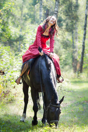 young beautiful brunette girl sit on a back of black horse green forest photo