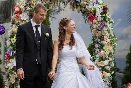 若い新郎と新婦の結婚式の花の結婚式のアーチの下に立つ 写真素材