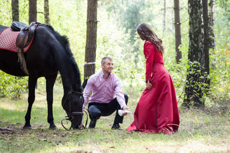 handsome man in pink shirt walk with young beautiful brunette girl in long red dress and black horse in green forest photo