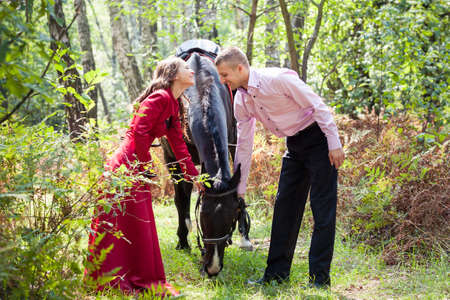 handsome man in pink shirt kiss young beautiful brunette girl in long red dress walk with black horse in green forest photo