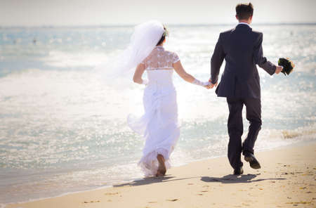 Bride with the groom walk along the sand to the sea photo