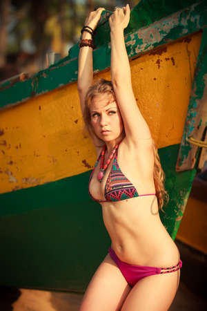 perfect waves: beautiful blonde girl in purple swimming suit pose near the wooden boat