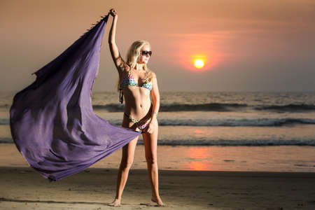 beautiful blonde girl in swimming suit with purple skarf stand on beach on sunset photo